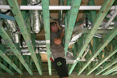Service technician repairing commercial ductwork.